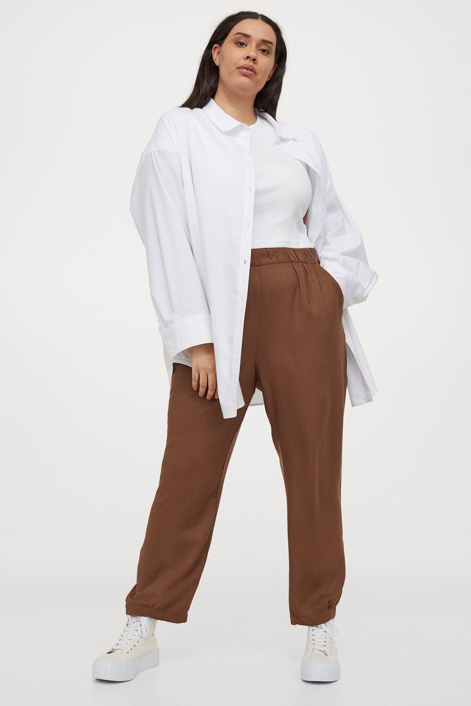 Pantalón tobillero en tejido vaporoso. Modelo de talle alto con elástico revestido en la cintura, bolsillos al bies y perneras globo con bajos ceñidos con pliegue