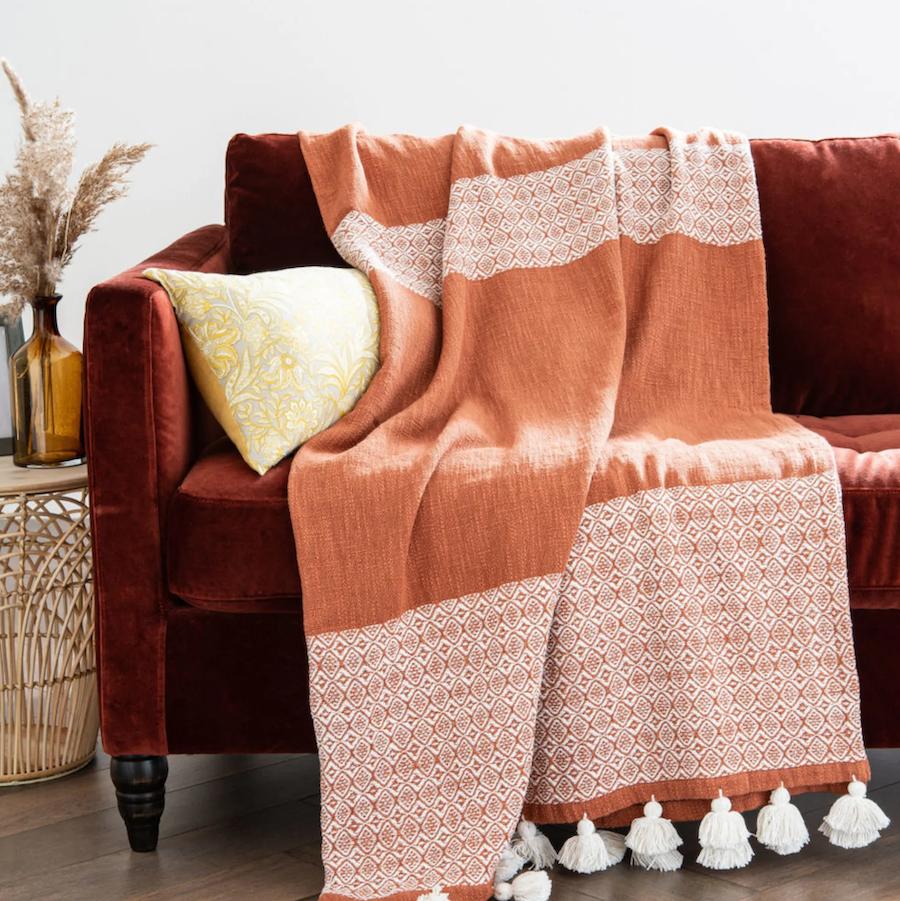 Manta de algodón terracota con motivos gráficos blancos y pompones 160x210