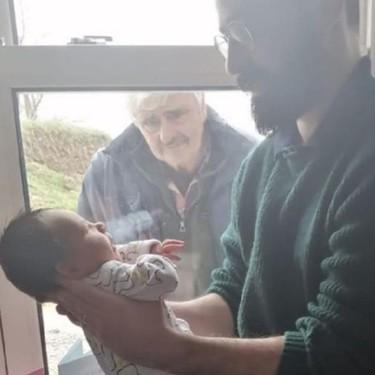 La conmovedora foto viral en la que un abuelo conoce a su nieto recién nacido en tiempos de coronavirus