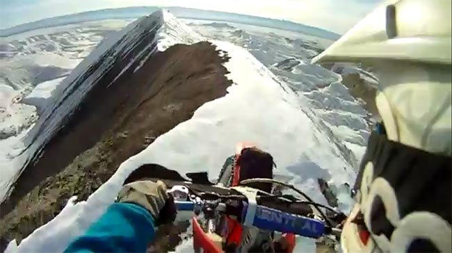 Moto cresteando por la montaña nevada