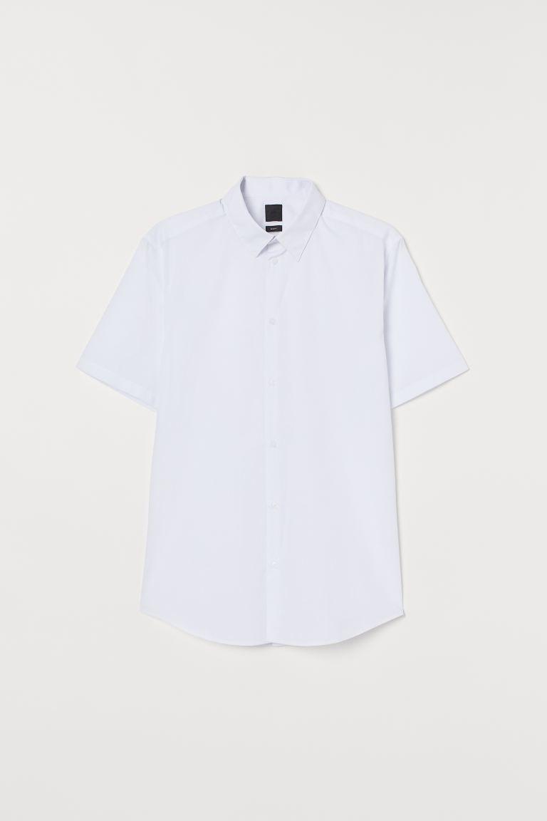 Camisa de manga corta en mezcla de algodón con cuello inglés, tapeta clásica y bajo redondeado. Corte ajustado para una silueta entallada, marcada en la cintura y estrecha en hombros.