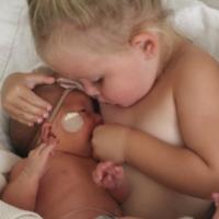 """El tierno vídeo de una niña pretendiendo """"amamantar"""" a su hermana recién nacida para calmarla"""