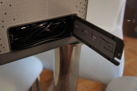 Compartimento para guardar el cable de alimentación e instrucciones de conexión por AirPlay