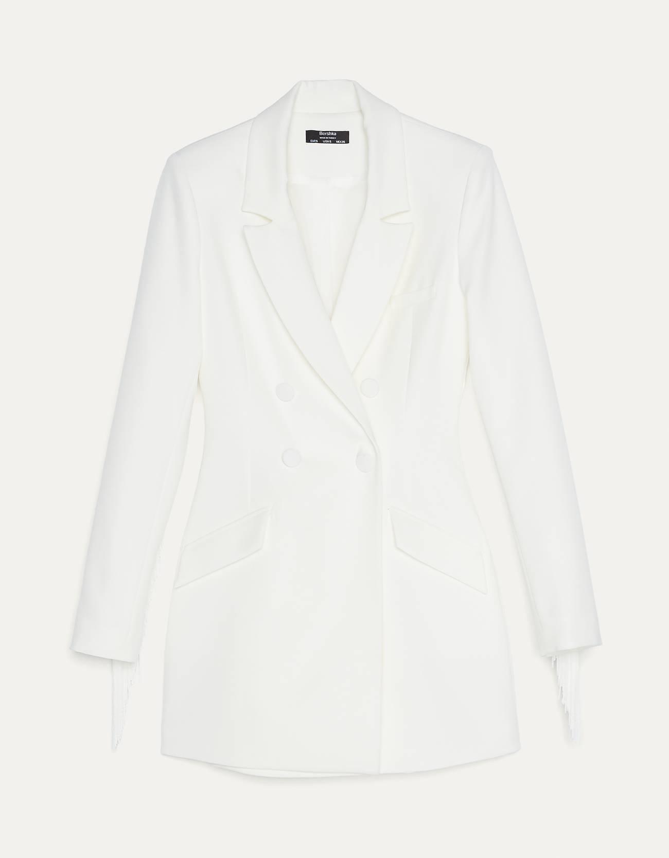 Vestido corto tipo blazer con cuello solapa y manga larga. Escote cruzado con botones frontales y bolsillos. Detalle de flecos en espalda.