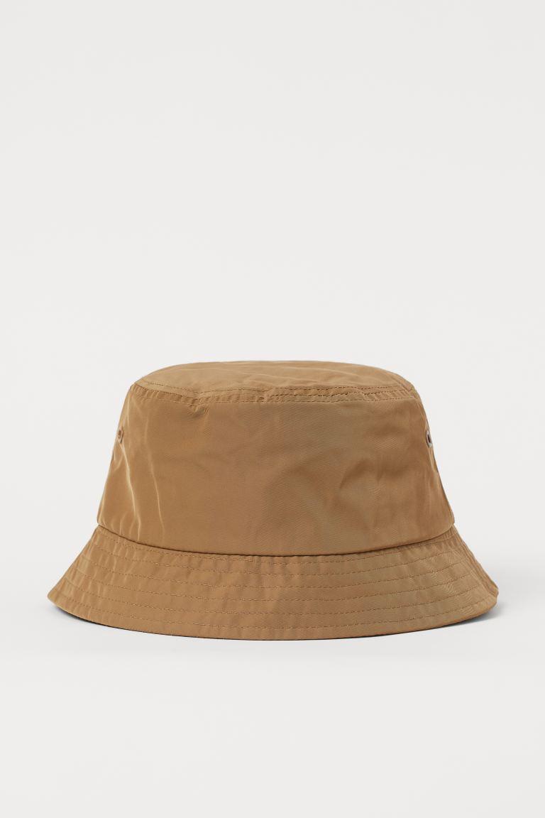 Sombrero bucket tejido con ligero brillo. Cinta antisudor y ojales de metal en cada lado.