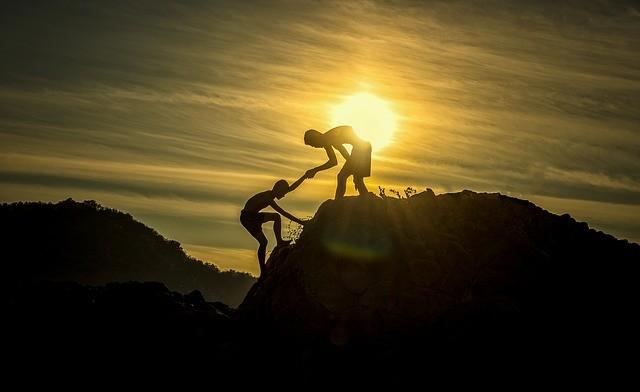 Chico ayuda a otro a subir una montaña.
