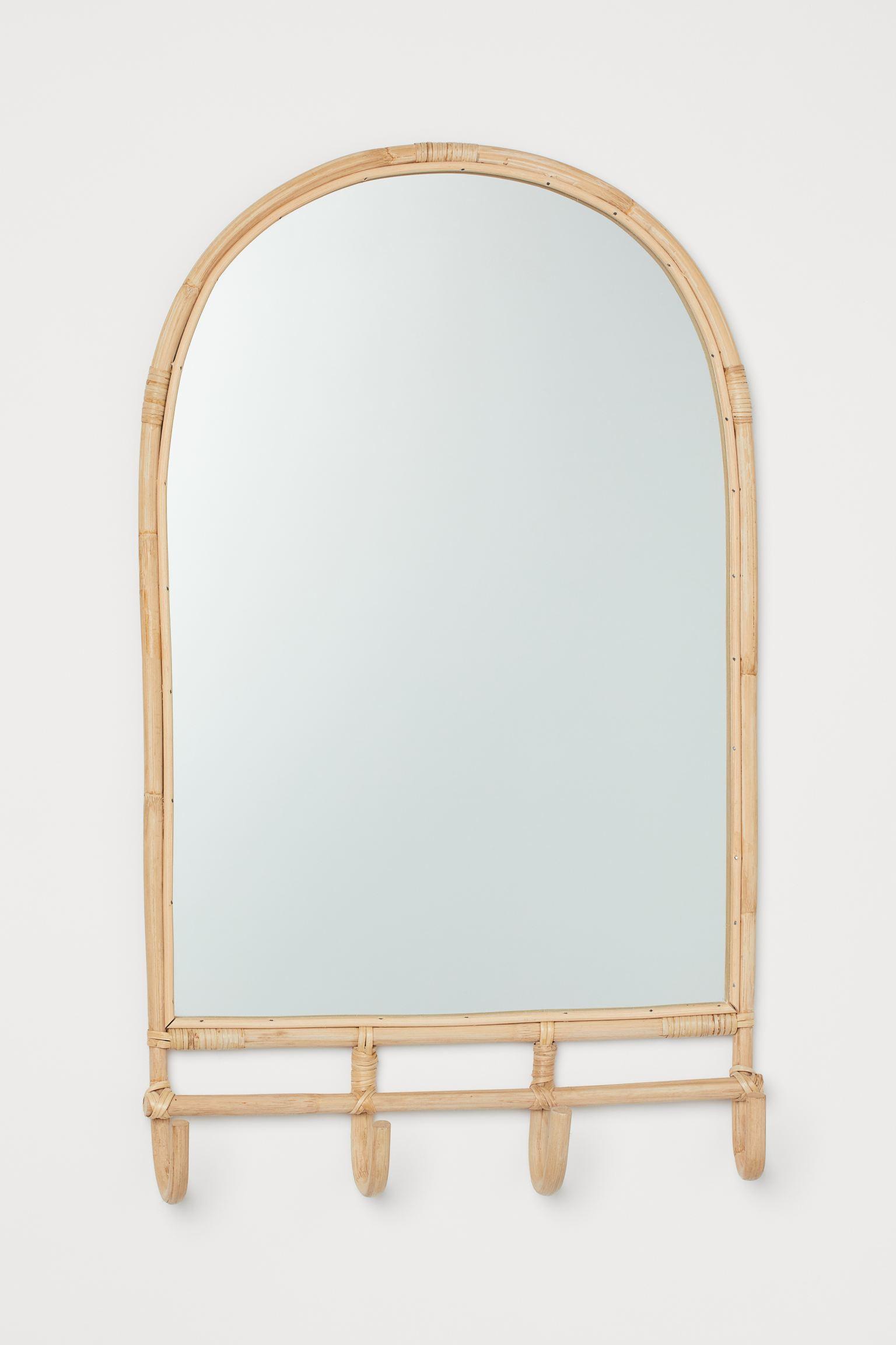 Espejo con marco de ratán, cuatro ganchos en la parte inferior y agujeros en la parte posterior para colgarlo.