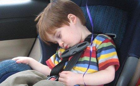 Niño durmiendo en el coche