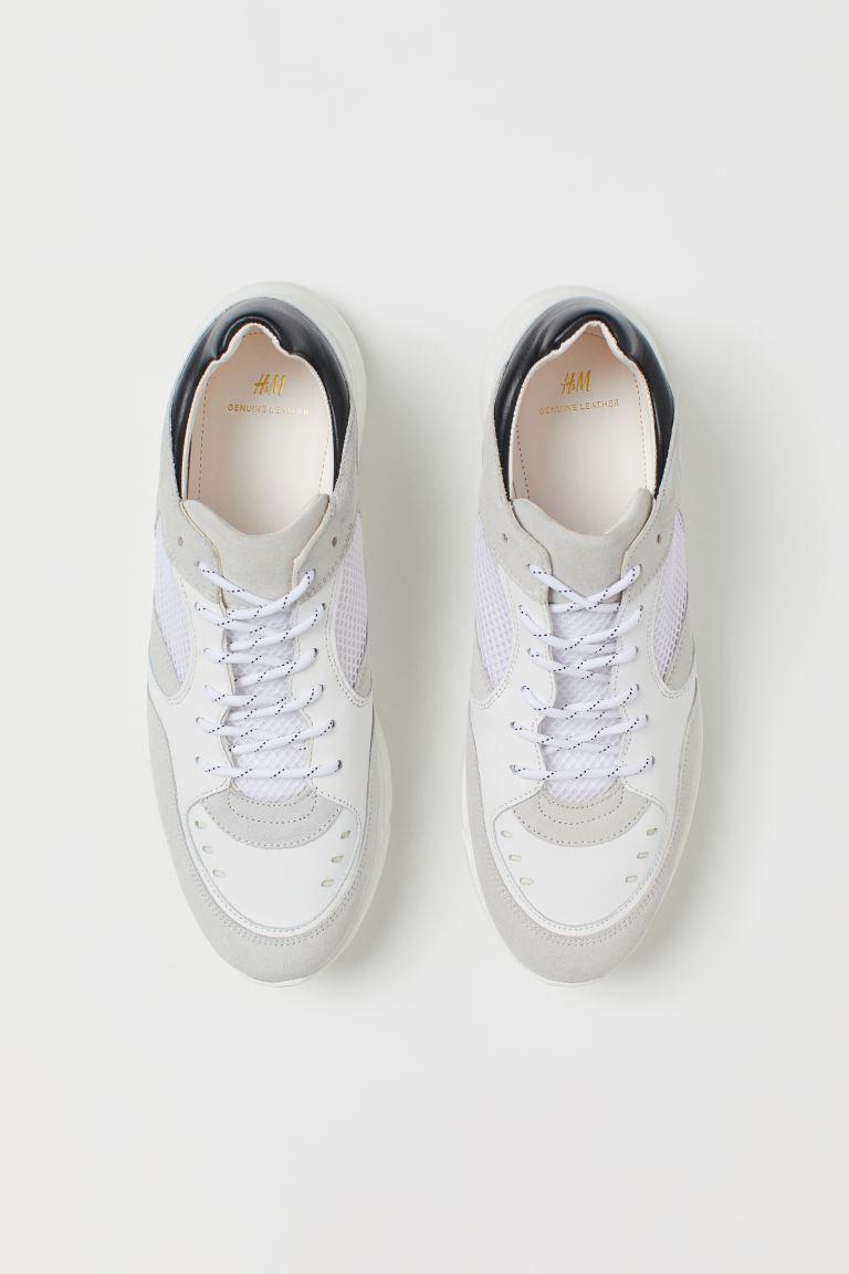 Zapatillas deportivas de piel con detalles de ante y malla. Collarín y lengüeta acolchados, y cordones. Forro y plantillas de piel. Suela gruesa con diseño.