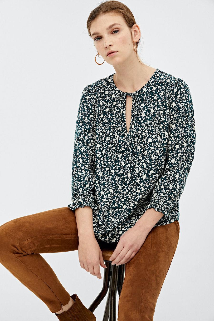 Blusa de manga larga con goma en puños, con escote en pico con detalle de cordón y con estampado de flores.