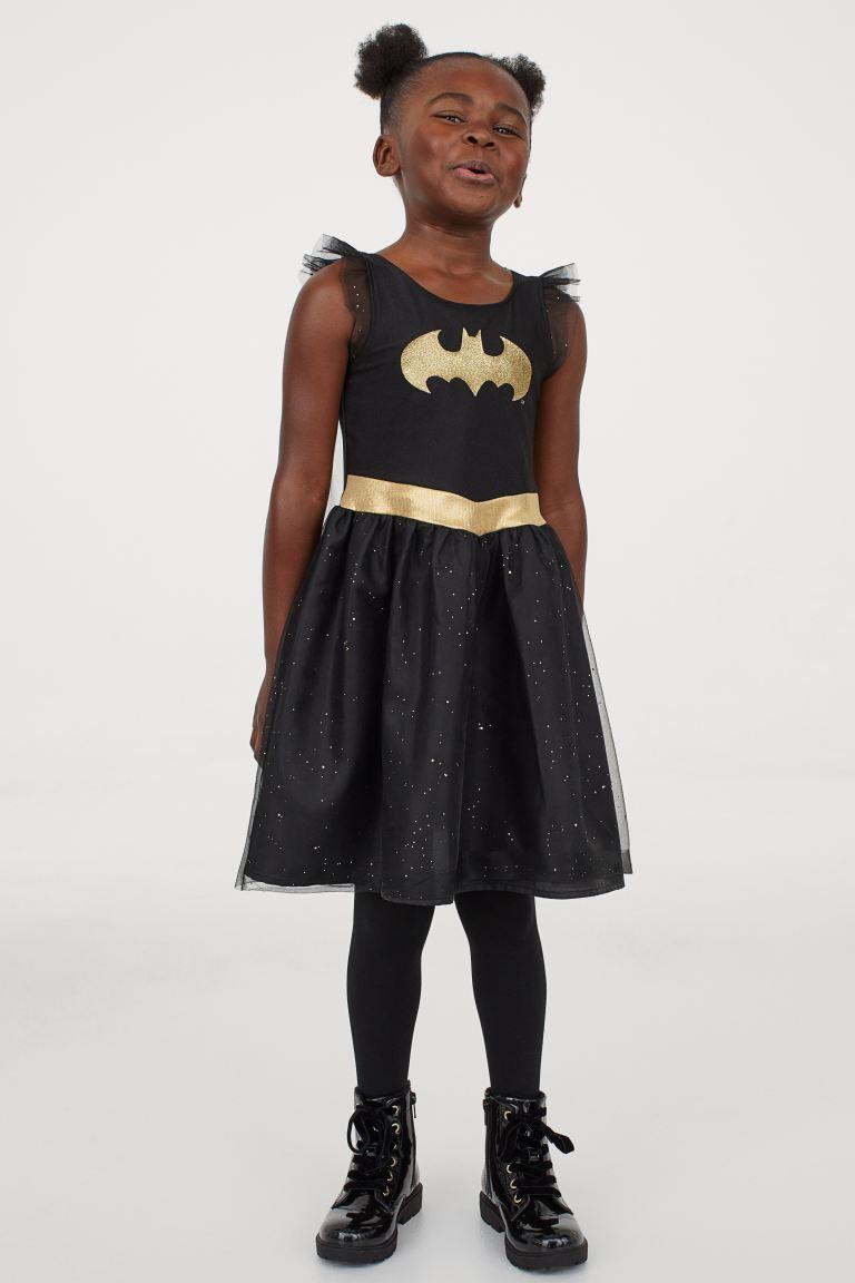 Vestido en punto brillante con motivo estampado delante, costura en la cintura y falda forrada con varias capas de tul, la superior brillante.