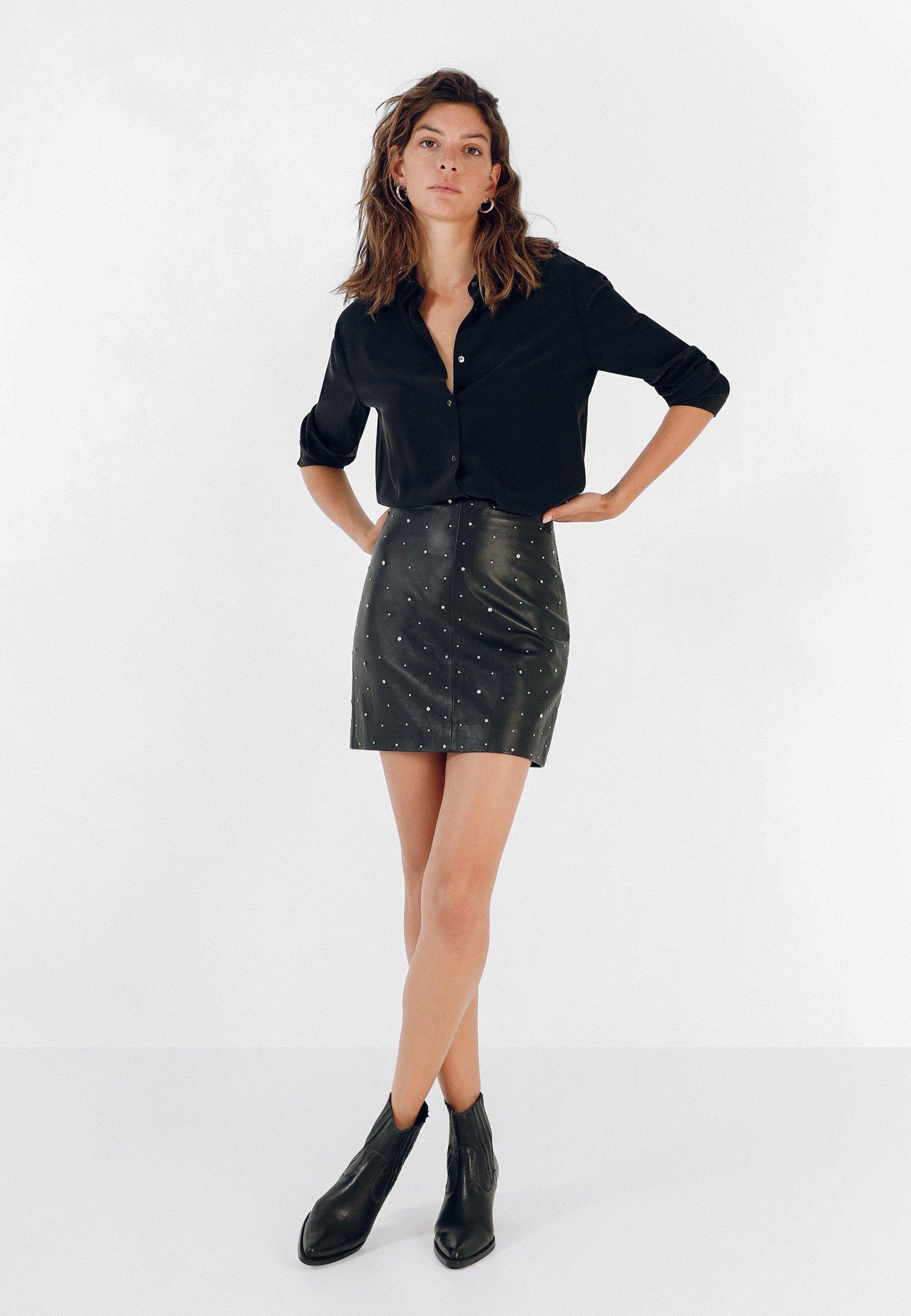 Mini falda de polipiel negra con tachas