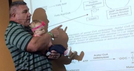 Un profesor sostiene en brazos a la bebé de una alumna que se había puesto a llorar