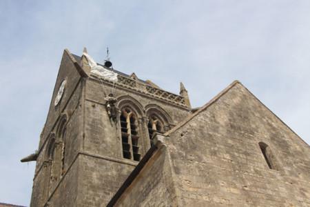 No es broma, de la iglesia de Sainte-Mère-Église cuelga un maniquí que representa a John Steele