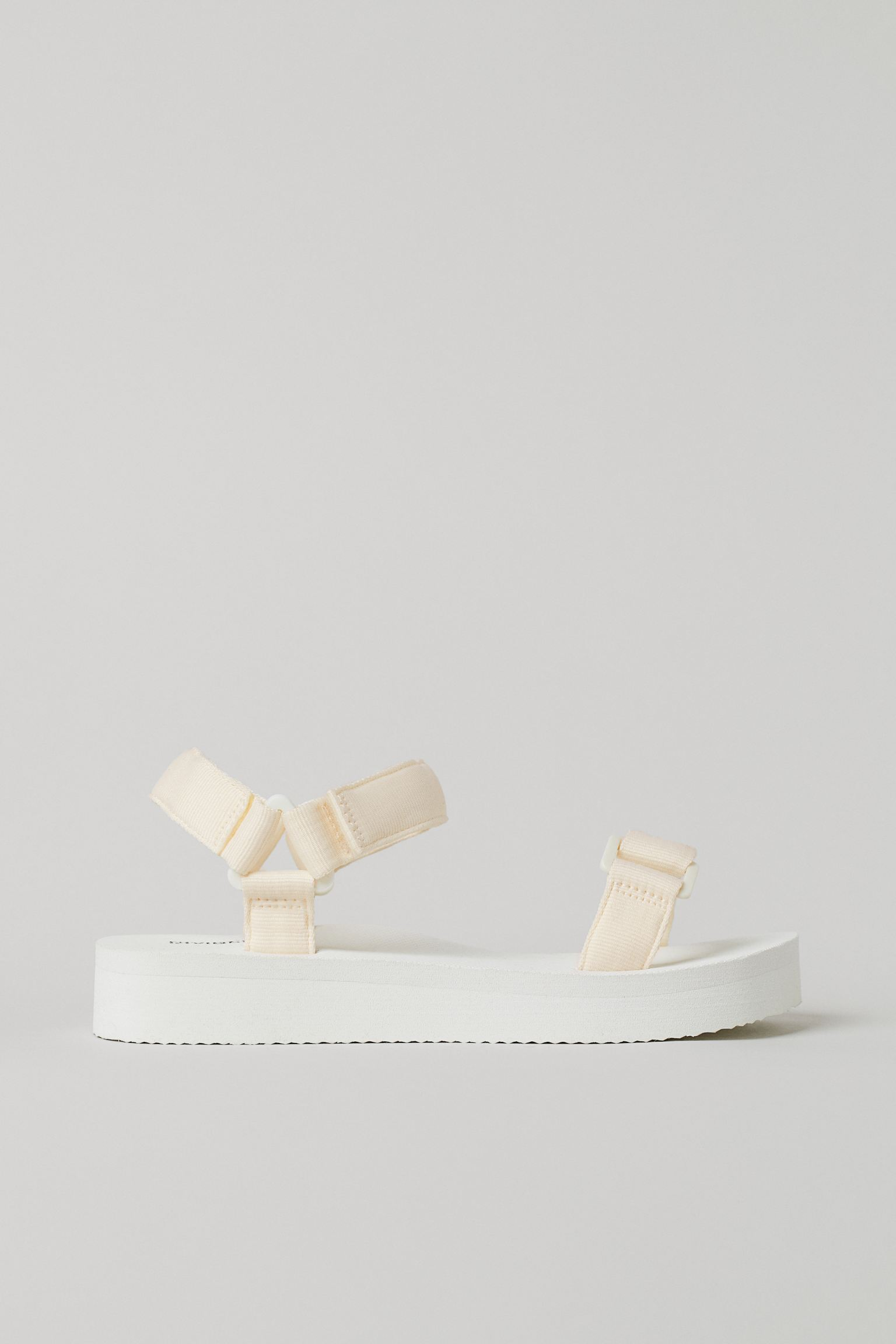 Sandalias con tiras ajustables con cierre autoadherente delante y en el tobillo. Suela de gomaespuma de 4 cm.