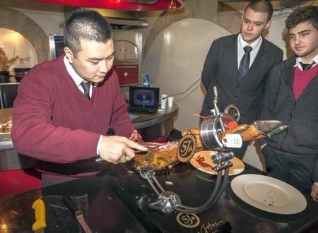 alumno de la Escuela de Hostelería Hofmann cortando Jamón de Bellota 100% ibérico