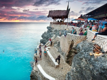 Ricks Caf In Negril Jamaicais An Iconic Drinking Institution Known For Its Epic Sunsets And The Many People Throwing Themselves Off Its Surrounding Cliffs The Well Known Beach Bar Is Perched On Some Epic Cliffs Above The Ocean And It Is A Popular Spo