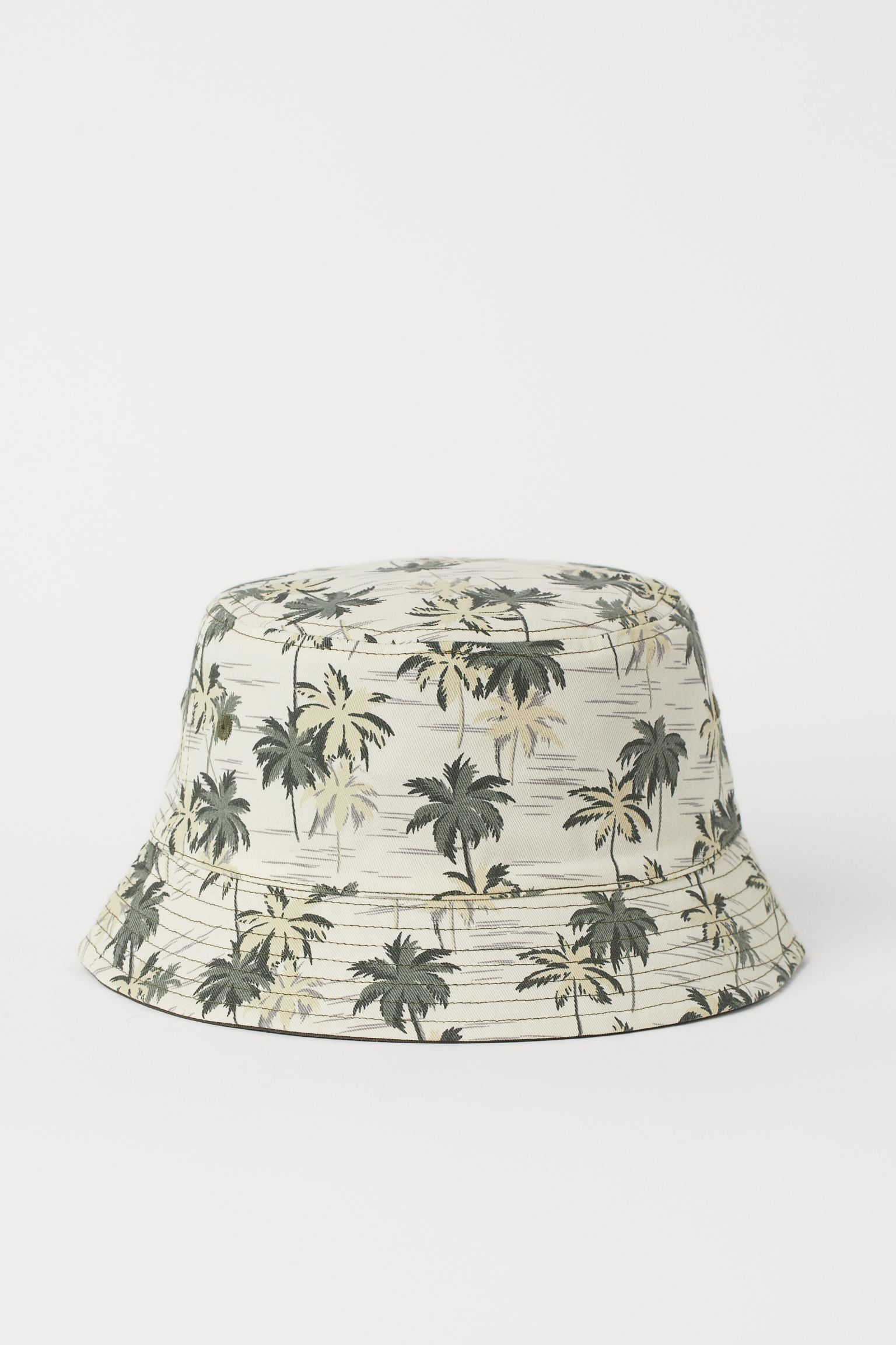 Sombrero reversible en sarga de algodón con un lado estampado y otro liso. Ojales bordados en cada lado.