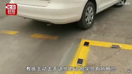 El sistema definitivo para aparcar bien: usar el móvil como rehén (y si te pasas de la línea pisas el móvil)