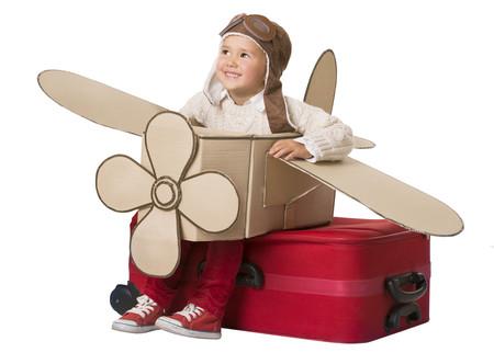 Niño de tres años con un avión hecho de cartón