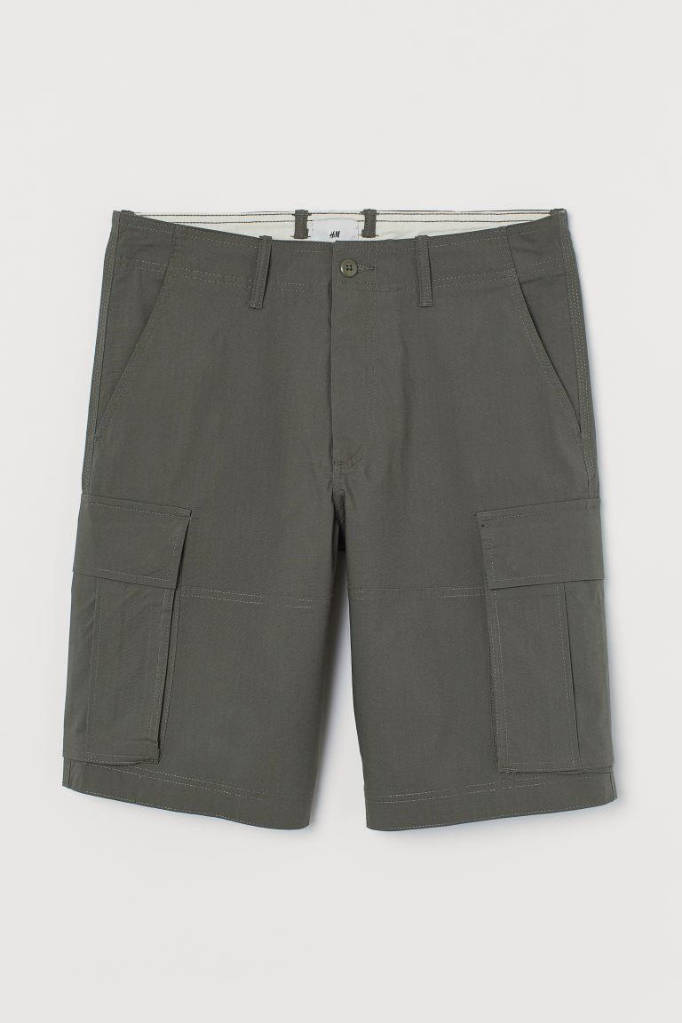 Pantalón corto en tejido resistente de algodón con cierre de cremallera con botón, bolsillos al bies, y bolsillos traseros y en las perneras con solapa y botón de presión.