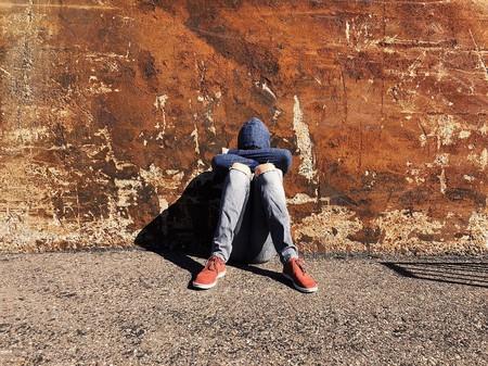 chico joven tapado con capucha sentado en el suelo, triste