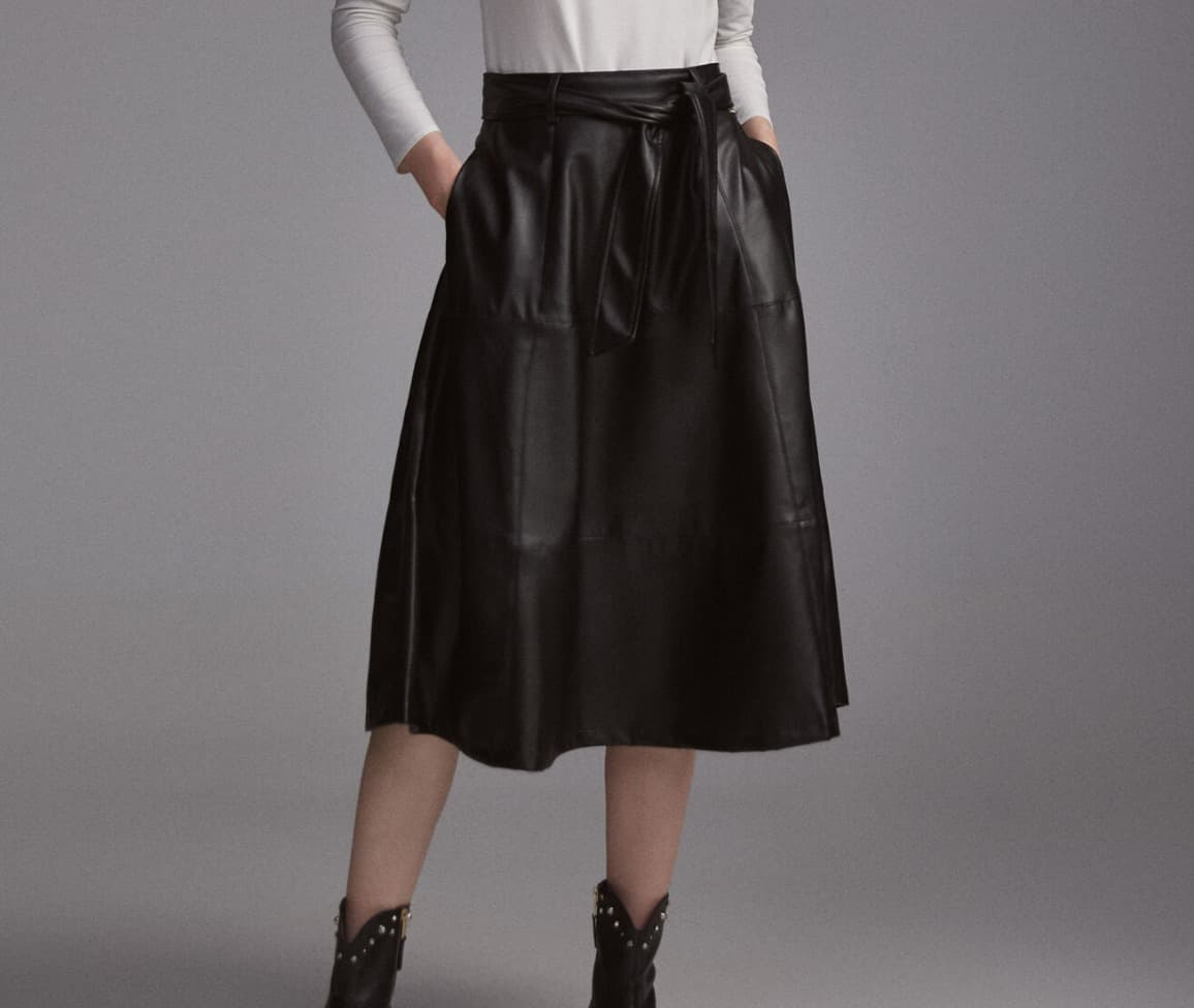 Falda midi en tejido efecto piel con cortes y pespuntes cargados sobre costuras. Cremallera en centro espalda para cerrar la prenda. Cinturón del mismo tejido para lazada.