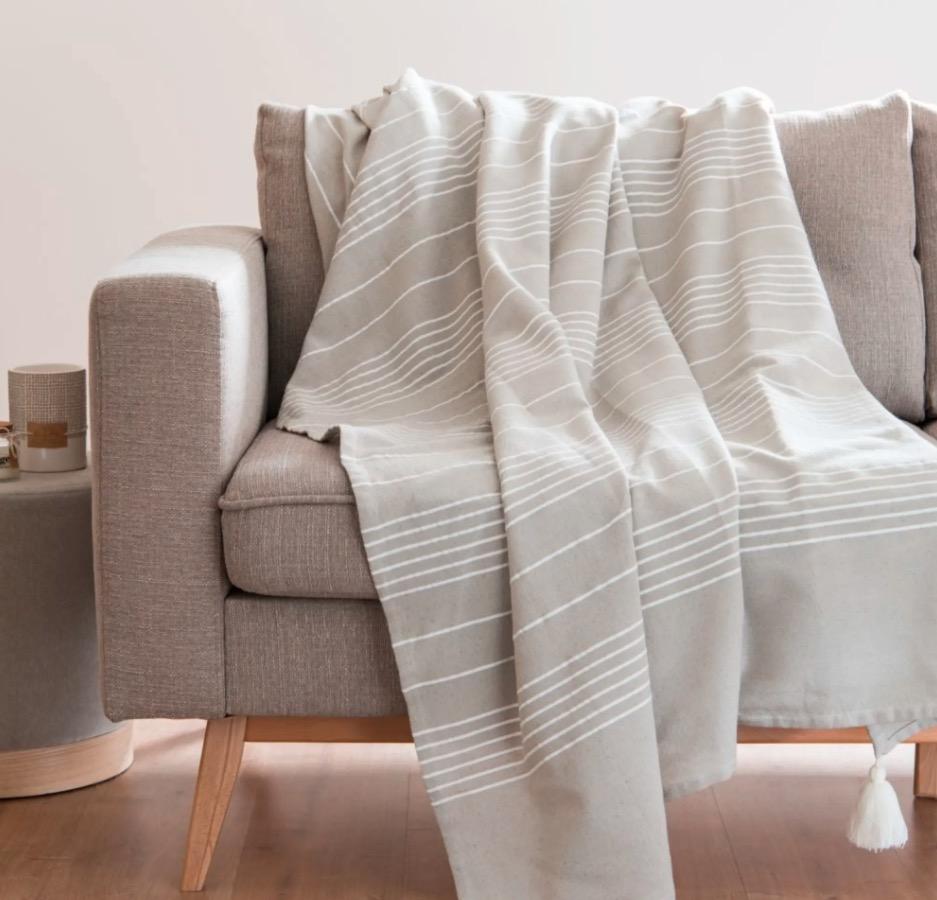 Manta con pompones de algodón de color gris y crudo 150x250