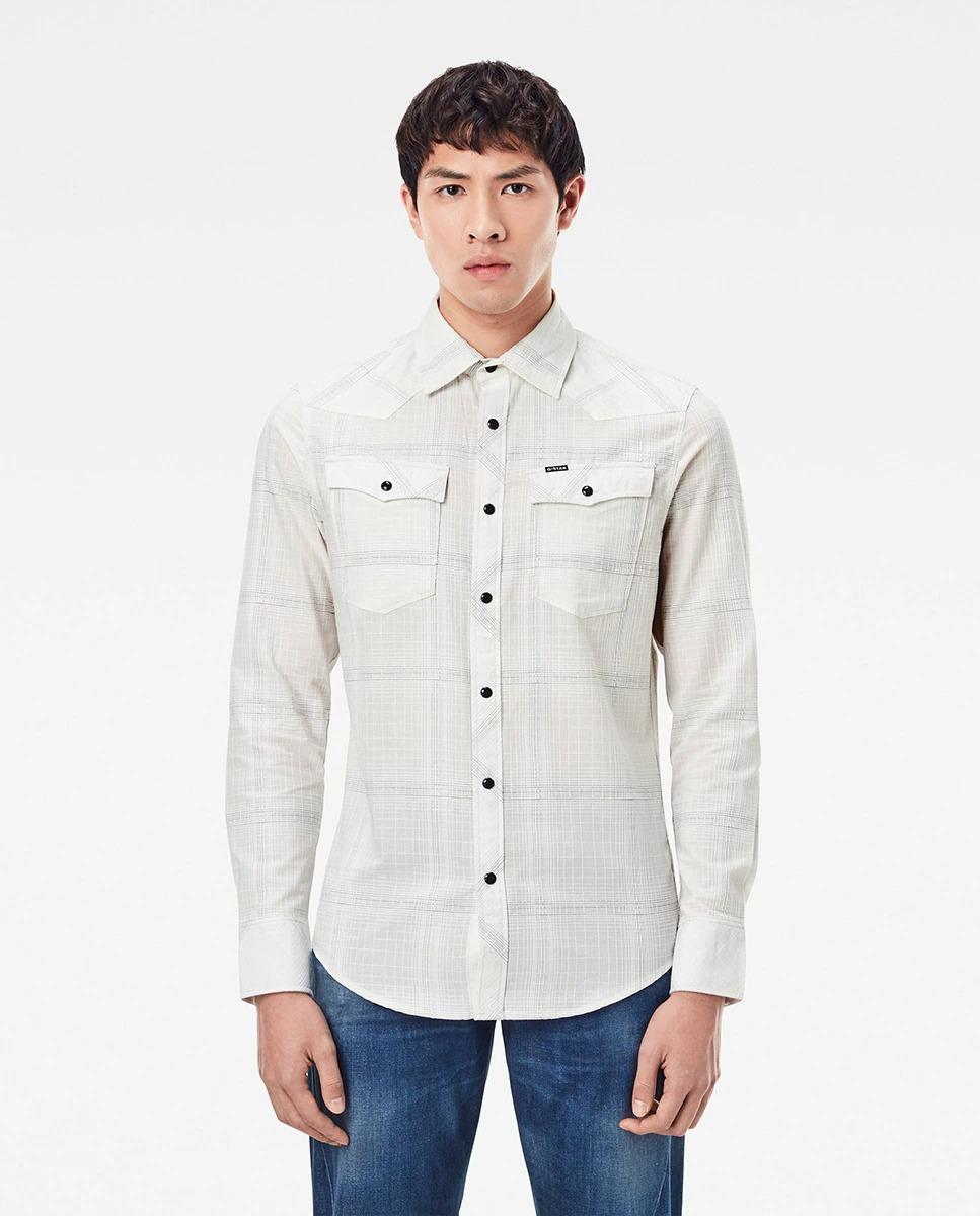 Camisa 3301 slim fit de color blanco con cuadros en algodón BCI. Está basada en una auténtica camisa del Oeste. Esta versión de corte ajustado está elaborada en un tejido a cuadros.