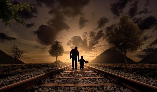 Padre e hijo caminan por la vía de un tren al atardecer.