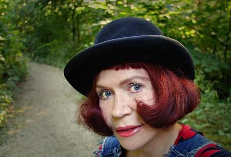 Mujer pelirroja con sombrero en la naturaleza.