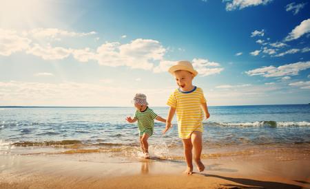 Dos niños pequeños corriendo a la orilla del mar