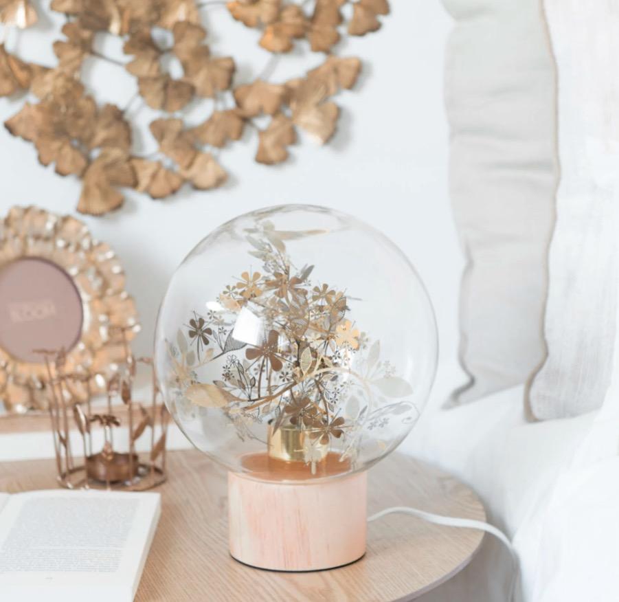 Lámpara bola de cristal con estampado de hojas de pino.