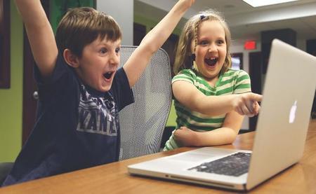 Niños contentos delante de un portátil. Ventajas de trabajar en casa con niños
