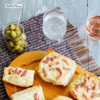 Tostadas de pan con queso Raclette y tocino. Receta de botana