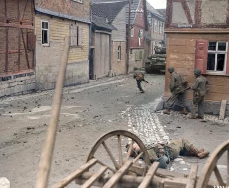 American Soldiers, Having Lost One Soldier, Trying To Cross The Street Under Cover Of Sherman Tanks Sniper Fire Is From The Upper Floors Of Buildings, Western Germany, Ca 1945