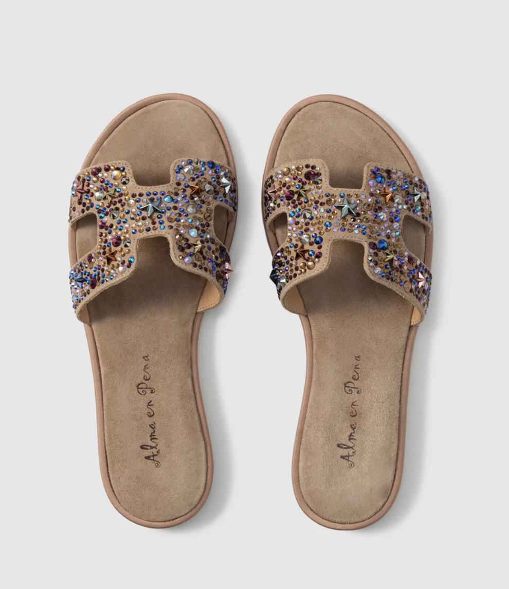 Sandalias planas en ante con adorno pedrería con forma H en la pala, tacón plano de 1 cm de altura y puntera redonda.