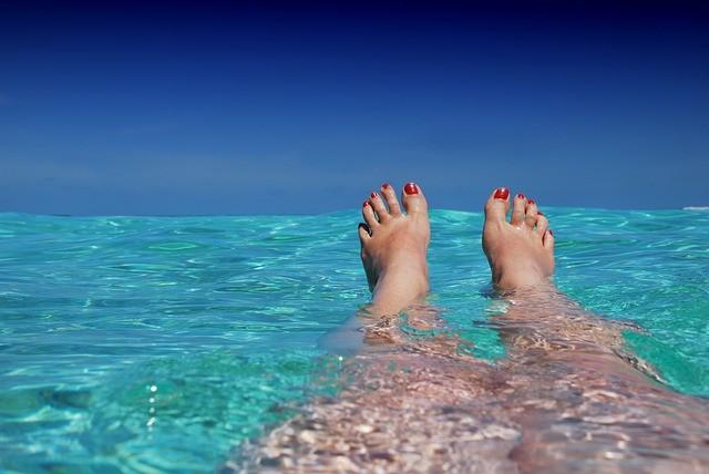 Pies en una playa paradisíaca.