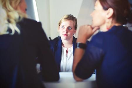 mujer en oficina con dos mujeres más