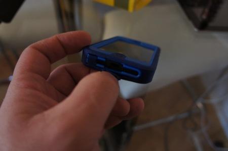 levantando la tapa de goma que protege el conector del cargador