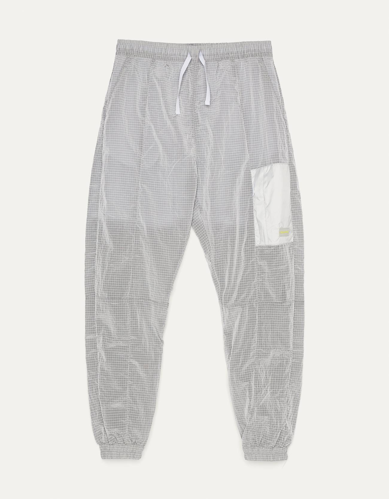 Pantalón jogger con tejido de nylon, cintura elástica ajustada por cordón y detalle de botones presión. Dos bolsillos en pernera y corte ligeramente fluido con goma en bajo.