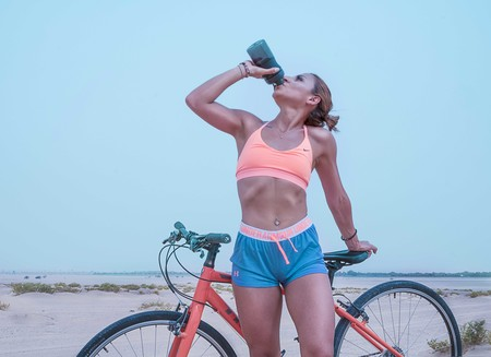 Woman Drinking Water While Standing Beside Her Bike 1302925 1