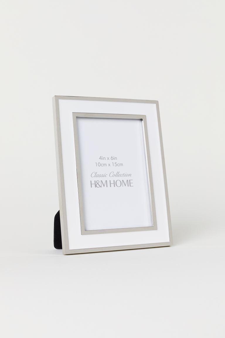 Marco fotográfico en metal brillante y vidrio transparente con soporte y colgador detrás. Tornillos no incluidos. Indicado para fotografías de hasta 9,5x14,5 cm. Medidas del marco 10x15 cm.