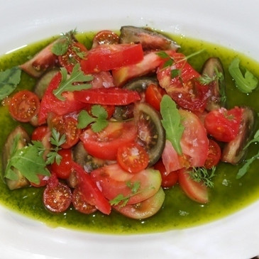 Ensalada de tomates sobre un lago de albahaca