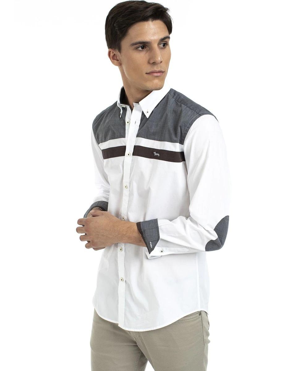 Camisa de corte custom de algodón con aplicación de canesú, parches en los codos e interior de los puños a contraste. Este modelo con botones en el cuello está adornado con un bordado del icónico teckel Blaine en el pecho.