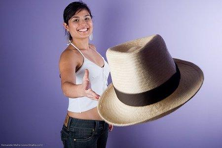 Chica lanzando su sombrero al aire.