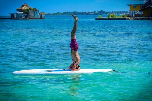 Stand up Yoga o Yoga sobre tabla de surf: en qué consiste y qué beneficios nos aporta el deporte acuático de moda