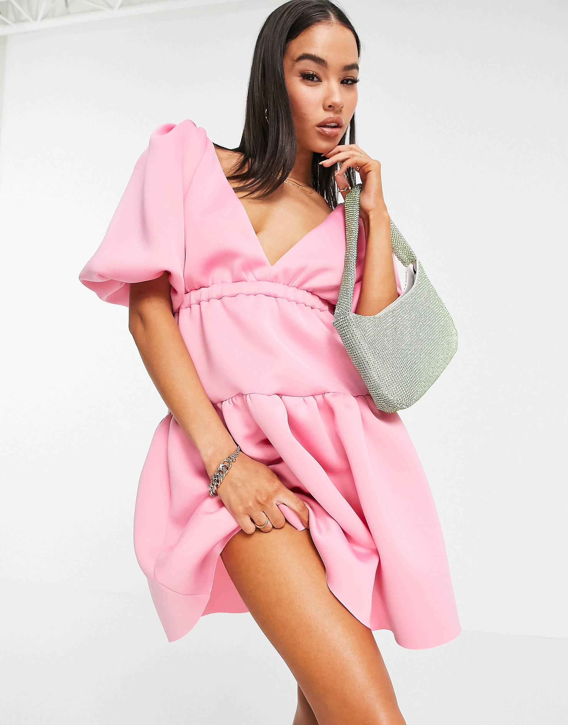 Vestido corto rosa chicle escotado de corte amplio elástico con mangas abullonadas.