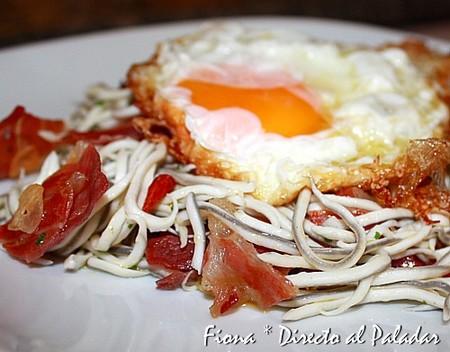 Huevos rotos sobre gulas y jamón crujiente. Receta