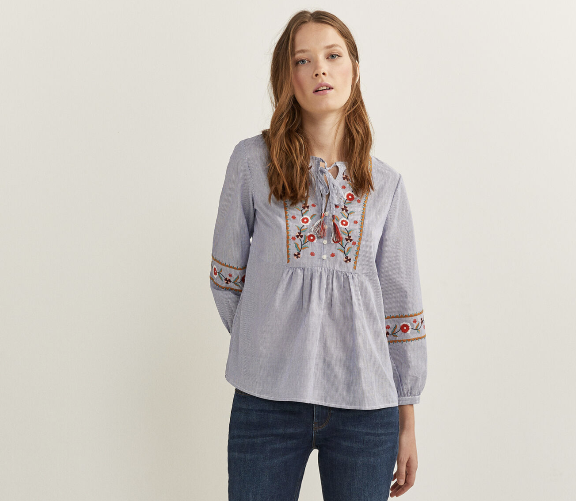 Blusa de manga larga con volumen, con cuello con abertura con botones y lazo con borla. Con bordados de flores en la parte delantera y en las mangas.